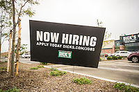 A now hiring sign outside of Dick's Sporting Goods store in Valley Stream, Long Island, New York during its grand opening sales on Saturday, July 9, 2016. Dick's recently purchased the intellectual property of its bankrupt competitor Sports Authority with a $15 million bid pending the courts' final approval on July 15.   (© Richard B. Levine)