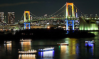 Spectacular Tokyo Rainbow bridge cityscape  with party boats all lit up at night.