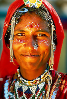 Smiling young woman, wearing ornate, traditional jewelry. Portrait. Headdress. Caste mark. Rajasthan India Asia.