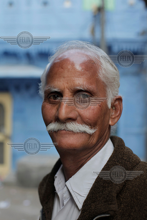 A man pose for a portrait in Jodhpur old city. Jodhpur is the second largest city in the Indian state of Rajasthan. Jodhpur is a popular tourist destination, featuring many palaces, forts and temples, set in the stark landscape of the Thar desert..The city is known as the Sun City for the bright, sunny weather it enjoys all year. It is also referred to as the Blue City due to the blue-painted houses around the Mehrangarh Fort.