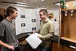 A Medford High School student discusses his light bulb experiment with a Tufts graduate student at the Medford High School science fair on Thursday, March 15, 2012. (Alonso Nichols/Tufts University)