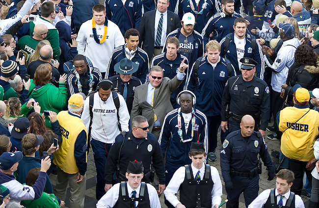 Nov. 17, 2012; Head coach Brian Kelly signals number one as he is greeted by fans on his way into Notre Dame Stadium with the team prior to the game against Wake Forest. Photo by Barbara Johnston/University of Notre Dame
