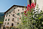 House with many windows and hollyhock flowers in the town of Stampa, Switzerland where Swiss sculptor Alberto Giacometti was born