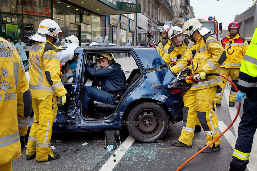 Switzerland. Geneva. Paquis neighborhood. A police officer holds the head of a wounded pregant woman seated on the driver's seat in a car accident on  the Chantepoulet street. Firefighters with helmets and yellow protective clothing work on a vehicle extrication, which is the process of removing a vehicle from around a person who has been involved in a motor vehicle accident, when conventional means of exit are impossible or inadvisable. A delicate approach is needed to minimize injury to the victim during the extrication. This operation is typically accomplished by using hydraulic tools, such as a cutter. The cutter is a hydraulic tool which is designed to cut through metal - a hydraulically powered shears. It is often called a crab-cutter, owing to the shape and configuration of its blades. Sometimes specified as to its capacity to cut a solid circular steel bar, these are most commonly used to cut through a vehicle's structure in an extraction operation. Cutter blades are replaceable, and blade development progresses as vehicle technology progresses in order to be able to cope with the new car protection technology.21.03.12 © 2012 Didier Ruef..
