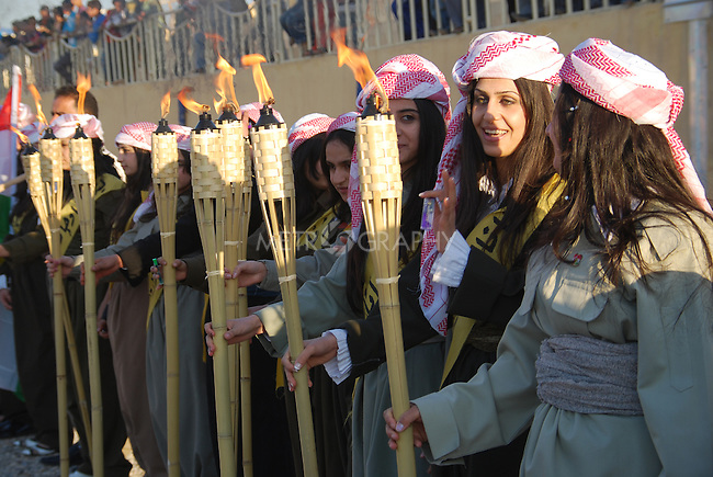 DOHUK, IRAQ:  Women dressed in traditional men's clothes hold torches...Newroz, celebrated across the world on the vernal equinox, is the official beginning of the Kurdish calendar and the first day of spring.  Kurds celebrate Newroz on March 20th and 21st by lighting fires and performing traditional dances...Photo by Ari Jalal/ Metrography