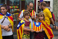 Boy and girl holding flag of Catalonia made with Lego on National Day of Catalonia, Barcelona, Spain
