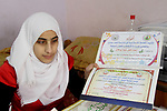 Asmaa Abu Hilal,18, a Palestinian blind studen displays certificates at her family house in Rafah in the southern Gaza strip on Feb. 14, 2017. Abu Hilal superior at her study although there are no private schools for the blind in the city of Rafah. Photo by Ebtehal Shurab