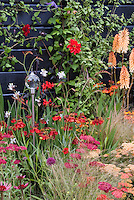 Hot colored theme garden with Achillea, Helenium, Crocosmia, Kniphofia, Dahlia, Echinacea, Gaura, ornamental grass