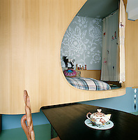 The apartment has a raised bedroom screened from the dining area by a curved wood panel turning the bed area into a secluded pod