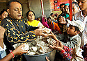 A charity group offers free food to poor people. Mass feeding is one of traditional Kumbh Mela practices.
