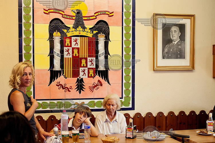 A family eats lunch at Casa Pepe, a restaurant where all the decor and menus are related to Franciso Franco and other fascist figures. What started as a genuine tribute to the dictator, has become a kitsch tourist attraction.