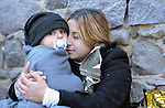 A refugee mother embraces her child on October 30, 2015, near Molyvos, on the Greek island of Lesbos, after landing from a journey in small boats across the Aegean Sea from Turkey. Local and international volunteers often provide the arriving refugees with food and medical care and dry clothes before they proceed on their way toward western Europe. Their boat to Greece was provided by Turkish traffickers to whom the refugees paid huge sums to arrive in Greece.