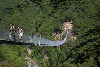"""Switzerland. Canton Ticino. Sementina valley. """"Caracs"""" Tibetan bridge. The 270 m long Tibetan bridge build by the Foundation Curzútt-S. Barnard allows the passage of the rugged valley that separates the communities of Sementina and Monte Carasso, two towns located in front of Bellinzona. The bridge joins the stone made village of Curzútt to the hiking path of """"Via delle Vigne"""", allowing people to make excursions in an area characterized by a landscape rich in cultural heritages. Anchored at a height of 696 m, the bridge rises 130 m above the ground. The walkway, large approximatively one meter, is made of larch wood. Crossing it is a unique experience that represents a true challenge. The safety measures guarantees a risk-free approach and make it a top-attractions either for young intrepid or adventurous families. 14.05.2015 © 2015 Didier Ruef"""