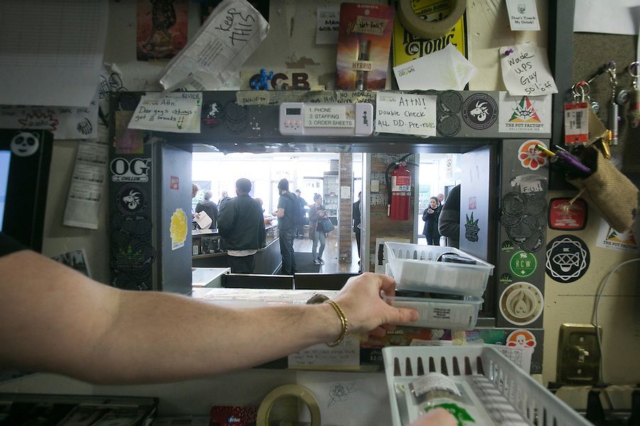 """Cashiers ring up sales as """"bud tenders' place orders through a window at Main Street Marijuana in downtown Vancouver February 14, 2017. (Photo by Natalie Behring for the Columbian)"""