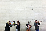 Music Academy students play in pedestrian passing near the main city square.