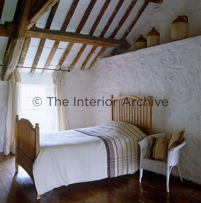 The guest bedroom is simply furnished with a wooden bed and Lloyd Loom chair