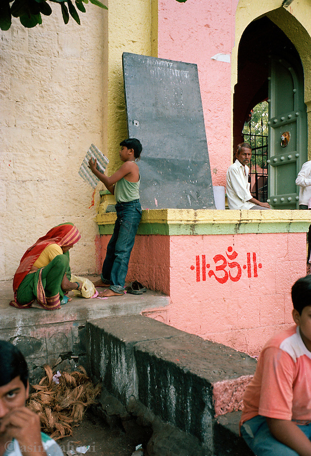Families rest and play at the gates of the Nagnath