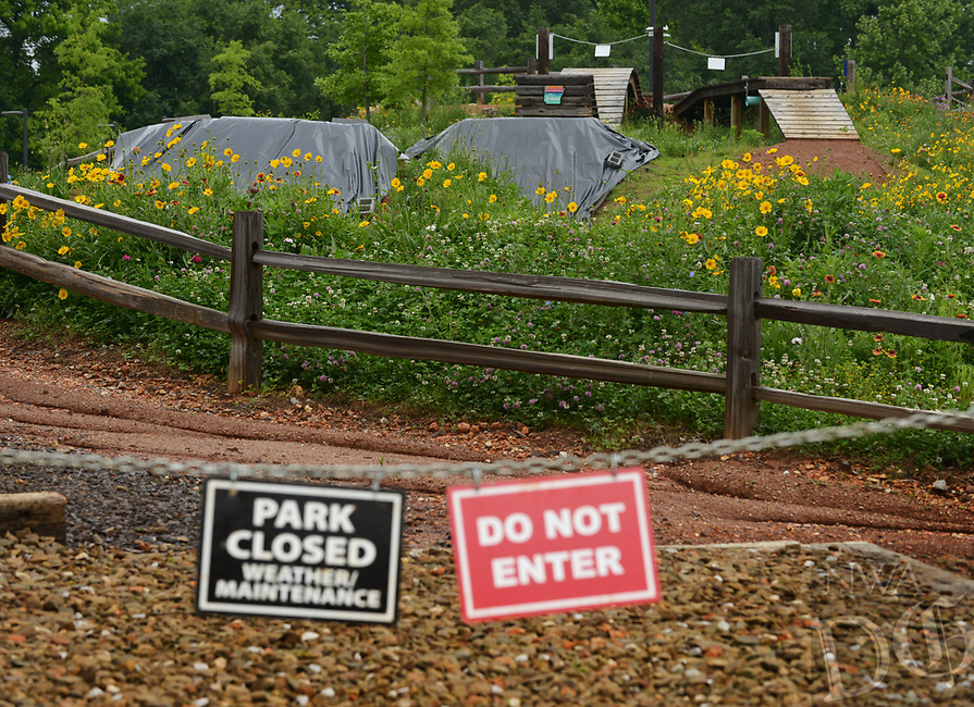 NWA Democrat-Gazette/BEN GOFF @NWABENGOFF<br /> Tarps cover the dirt jumps Friday, May 12, 2017, at The Railyard Bike Park in Rogers, which has been closed since heavy rain in April. Rogers plans to reopen some of Lake Atalanta park South of Walnut Street on Saturday, but The Railyard will remain closed for the time being.