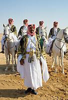 Bedouins with horses in the desert in Saudi Arabia