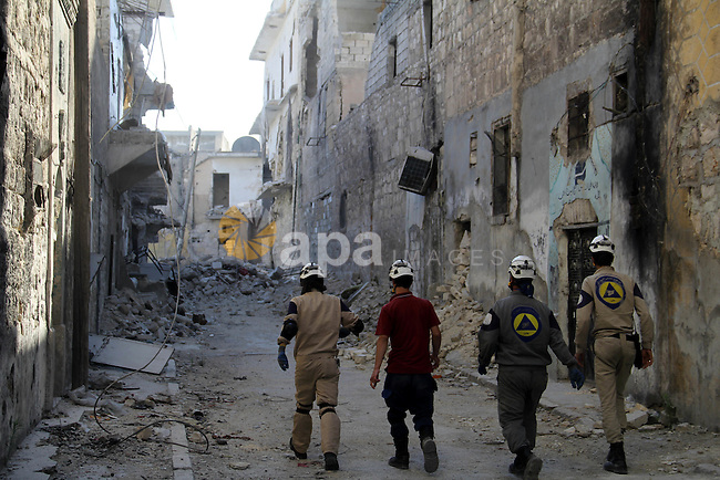 Syrian civil defense members run in a street following a reported bomb barrel attack by Syrian government forces in Bab al-Nairab district in the northern Syrian city of Aleppo, June 30, 2015. Photo by Ameer al-Halbi
