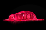New car on a stand under red fabric presentation concept isolated on black background