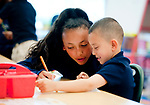 WATERBURY,  CT-051617JS04- Iyanna Figueroa, 14, a member of the Duggan School student council, helps kindergarden student Eric St. Hilaire, with some math problems during school on Tuesday. Jim Shannon Republican-American