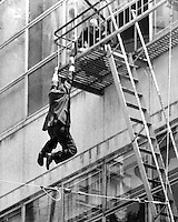 Man hangs from the fourth floor fire escape of Hastings Dept. store at 15th &amp; Broadway in downton Oakland, California. Policeman grabs his wrist and deflected him as he fell into the thired floor fire escape below. Man was not seriously injured.  <br />(photo copyrighted 1960 by Ron Riesterer, Oakland Tribune)..