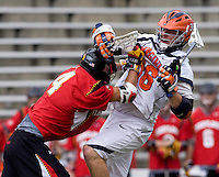 Brian Carroll (36) of Virginia is hit by Dan Burns (4) of Maryland after a shot during the ACC men's lacrosse tournament finals in College Park, MD.  Virginia defeated Maryland, 10-6.