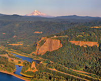 View of Rooster Rock and Vista House on Crown Point in Columbia River Gorge National Scenic Area with Mt Hood on horizon in Oregon
