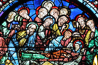 The 12 apostles surrounding the body of the Virgin, the Death of the Virgin, from the Glorification of the Virgin stained glass window, 13th century, in the nave of Chartres cathedral, Eure-et-Loir, France. Chartres cathedral was built 1194-1250 and is a fine example of Gothic architecture. Most of its windows date from 1205-40 although a few earlier 12th century examples are also intact. It was declared a UNESCO World Heritage Site in 1979. Picture by Manuel Cohen