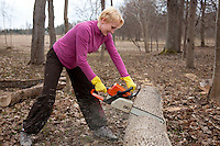 Happy Emotional Caucasian Woman Cutting Log with Chainsaw