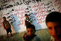 Palestinian children play in front of a wall covered with names of their killed countrymen near the Jewish settlement of Neve Dekalim, southern Gaza Strip September 4, 2005. Israeli Prime Minister Ariel Sharon and Palestinian President Mahmoud Abbas will meet this month, their first summit since Jewish settlers were evacuated from occupied Gaza, an Israeli newspaper said.  REUTERS/Damir Sagolj