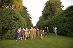 Old Westbury, New York, U.S. - June 21, 2014 - Lori Belilove & The Isadora Duncan Dance Company and visitors are walking up the South Allee, a sweeping walkway flanked by evergreens, towards the South Lawn in front of the back of the mansion, shortly before the modern dancers perform their finale of Midsummer Night event at the Long Island Gold Coast estate of Old Westbury Gardens on the first day of summer, the summer solstice. Ms. Belilove is at far left and wearing a white tunic and purple over-scarf.