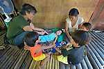 In Abucay, a seaside town in the Philippines province of Bataan, Joy Morada (left) helps 5-year old JZ Arilla with exercises that help her deal with her cerebral palsy. The girl's mother, Joselyn, and one-year old brother Angelo, along with two neighbor children, observe. Morada is president of the local Persons with Disabilities (PWD) organization.