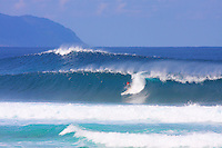 A surfer pulls into a decent size wave at Backdoor on Oahu's North Shore. A back wave is rising up in the background at Off the Wall.