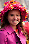 A girl wearing a hat covered in pink flowers in the New York City Easter Parade