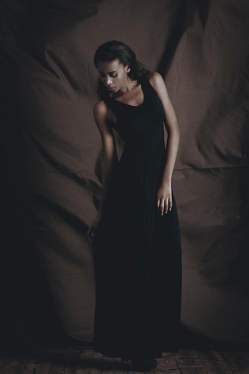Black female model wearing black clothes posing for fashion shoot
