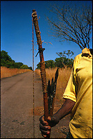 Near Lungue Bungo, Angola, May 2006.A traditional hunter on a road not yet cleared from landmines. Just 4 years after the end of a 25 year long civil war, Angola is starting to emerge again, yet a lot remains to be done: entire regions are still cut-off from the ouside world because of landmines and broken bridges, over 80% of the population lives below the poverty threshold in one of the potentially richest country in Africa. Natural ressources include oil, diamonds, gold and...water!.Malaria, tuberculosis, HIV/Aids are endemic, cholera and meningitis frequent.
