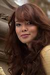 Laurence Yang with long auburn hair and great look of mischief. Yellow blouse.  Laurence is an exotic beauty of French and Korean descent.
