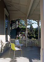 A pair of contemporary chairs on a traditional covered porch