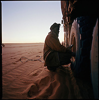 Sahara desert, Libya-Chad, November/December 2004..Every week, a convoy of 40 privately owned Libyan trucks loaded by the WFP with about 1000 metric tons of western food aid cross 2500 km of deep desert across Libya and Chad to reach more than 200 000 refugees from Darfur in camps near the Sudanese border. Abdallah, a Sudanese mechanic, has to adapt tyre pressure to the type of sand encontered dozens of times every day...each truck has 10 tyres...it is a very lenghty process...