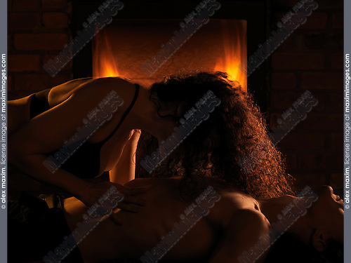 Sensual portrait of a couple making love in front of a fireplace, woman caressing man's body