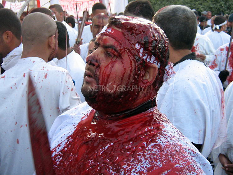 KARBALA, IRAQ: A devout Shia, covered in blood, beats himself with a knife on Ashura, the day of mourning for the death of Imam Hussein...Photo by Sami Al-Hilali/Metrography
