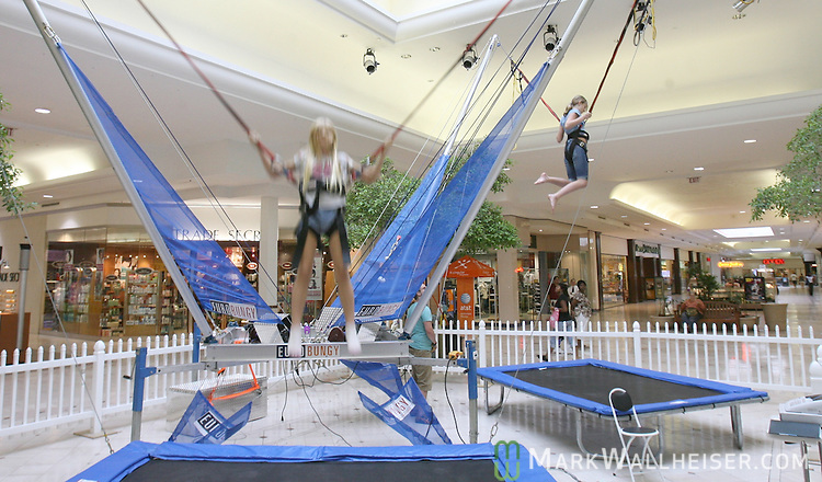 Phoebe French, left, 9 years-old, and her sister Flannery French, right, 12 years-old bounce up and down on the Euro Bungy in center court at the Tallahassee Mall in Tallahassee, Florida September 13, 2007.  (Mark Wallheiser/TallahasseeStock.com)
