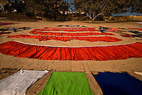 Wet shiny fabrics dyed in bright colours are spread out on the ground to dry along the banks of the Ganges.<br /> (Photo by Matt Considine - Images of Asia Collection)