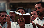 Shiite Muslims read from book of recitations about Imam Moussa Kadhim outside the Khadimiya shrine September 22, 2003 in Baghdad, Iraq to mark the anniversary of the death of the Imam Moussa Kadhim.