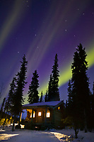 Aurora borealis arcs over Windy Gap log cabin in the White Mountains National Recreation Area, interior, Alaska