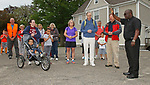 Torrington, CT 052017MK03 Father William Agyemang blesses about thirty parents, supporters and students of the St. Peter/St. Francis School before they begin walking along main Street in Torrington Saturday morning. The  The 7.1 mile walk started from the school's campus to end at the Lourdes Shrine in Litchfield.  Kristen Harmon said that the walk was to help raise awareness of Catholic education in Torrington and how they can serve the community with their focus on spirituality and an awareness of the importance of family. Michael Kabelka / Republican-American
