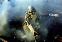 A worker welds a large piece of metal in the ship-breaking yard in Gaddani.