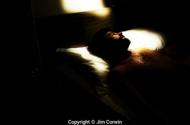 Downtown Hotel room at night with man lying on bed with throat cut